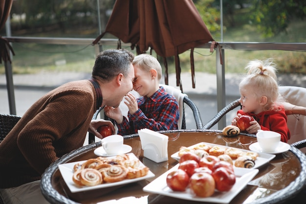 Couple marié avec enfants, fille et fils à une table dans un café. heureux couple traditionnel, bonheur familial.