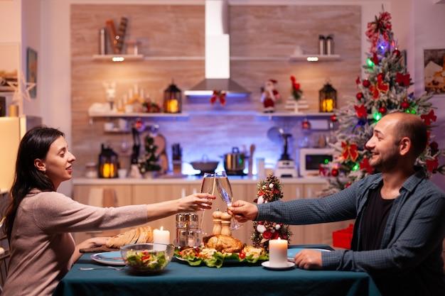 Couple marié frappant un verre de vin assis à table à manger