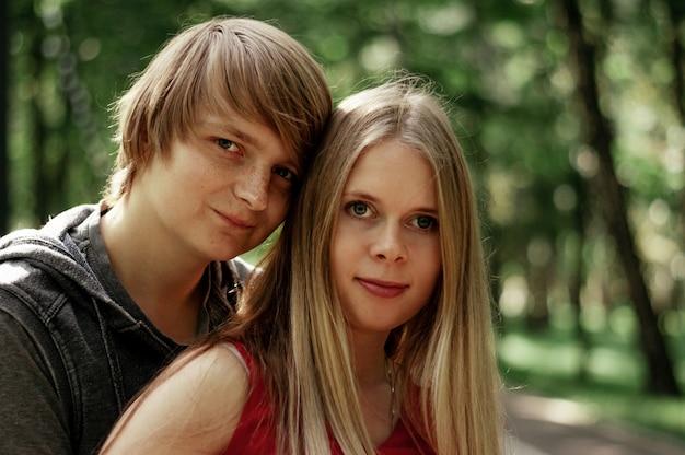 Un couple marié heureux embrasse une belle femme adulte. promenades dans un parc.