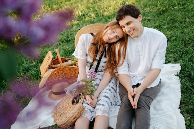 Couple marié heureux en vacances dans les amoureux du parc en été sur un pique-nique assis sur une couverture