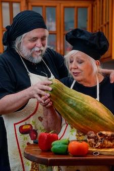 Couple marié homme et femme cuisinant joyeusement dans la cuisine à la maison