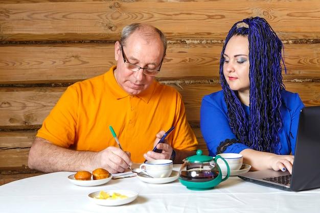 Un couple marié homme à lunettes et une femme avec des tresses afro bleues à la table travaillent à l'ordinateur