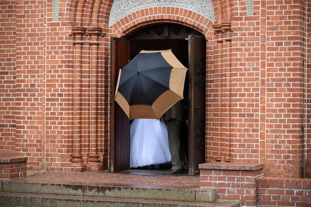 Couple marié de jeunes mariés derrière un parapluie sur la porte de l'église le jour de la cérémonie de mariage par temps de pluie