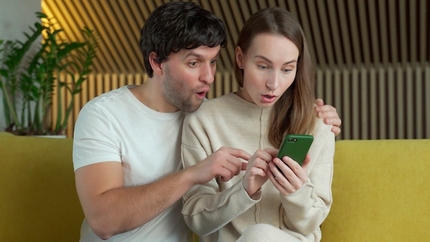 Couple marié regardant l'écran du smartphone, célébrant la notification de gain de loterie en ligne.