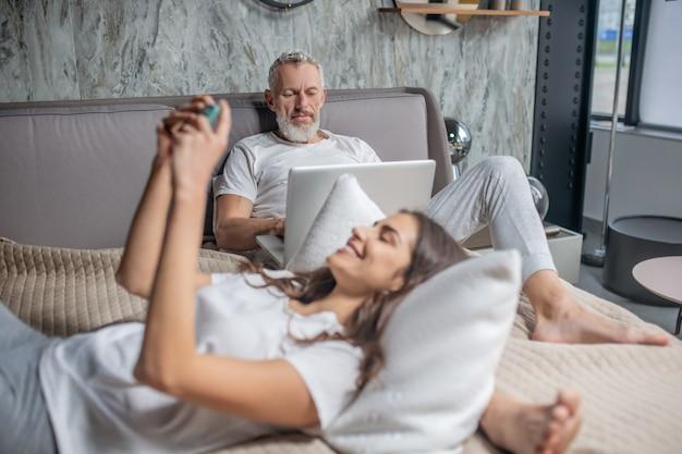 Un couple marié. sérieux homme aux cheveux gris attentif travaillant sur ordinateur portable et joyeuse jeune femme avec smartphone couché dans la chambre