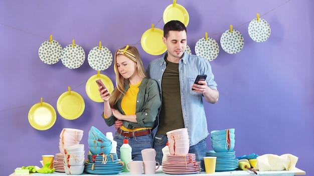Couple marié travailleur, femme et mari sont debout près d'une table avec un tas de vaisselle sale