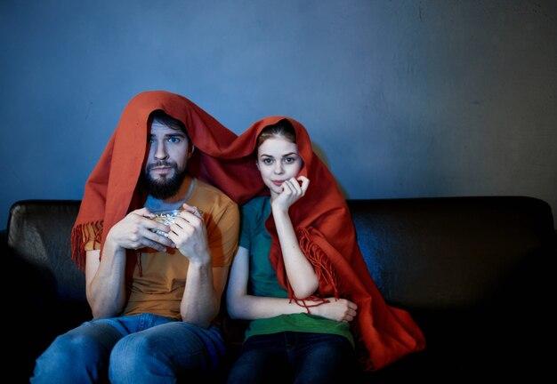 Un couple marié va décoller sur le canapé recouvert d'une couverture devant le support télé