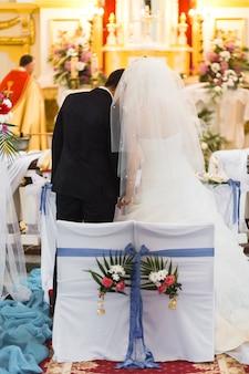 Couple marié vu de dos dans la cathédrale pendant la cérémonie de mariage