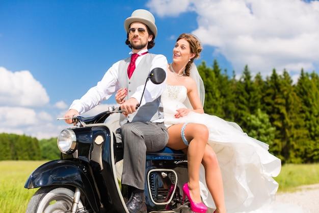 Couple de mariée conduisant un scooter de moteur portant une robe et un costume
