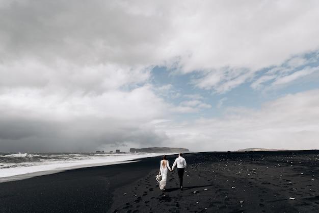 Un couple de mariés marche le long de la plage noire de la plage de sable de vic avec du sable noir sur les rives