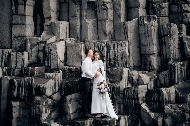 Un couple de mariés se dresse sur un mur de piliers en pierre. les mariés s'embrassent sur le basalte kekurs, sur la plage de sable noir de vik. mariage à destination de l'islande.