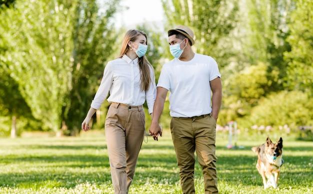 Couple avec masque de protection marchant dans le parc