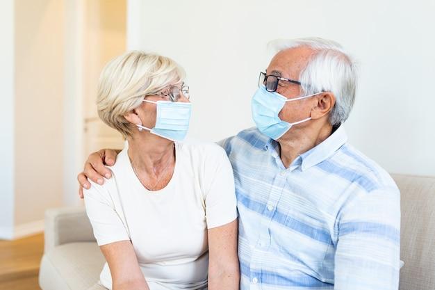 Couple avec masque de protection en quarantaine à la maison