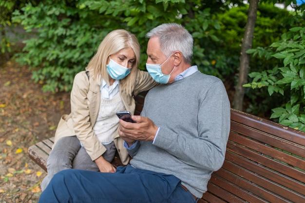 Couple masqué utilisant un téléphone portable ensemble dans le parc pendant la pandémie de coronavirus