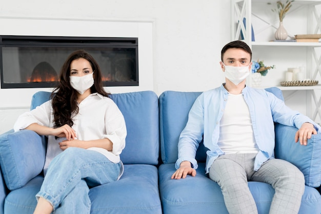 Couple avec masques à la maison sur le canapé