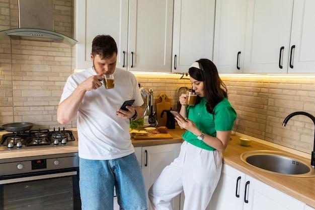 Couple le matin à la cuisine prenant son petit déjeuner surfer sur internet sur l'espace de copie de téléphone