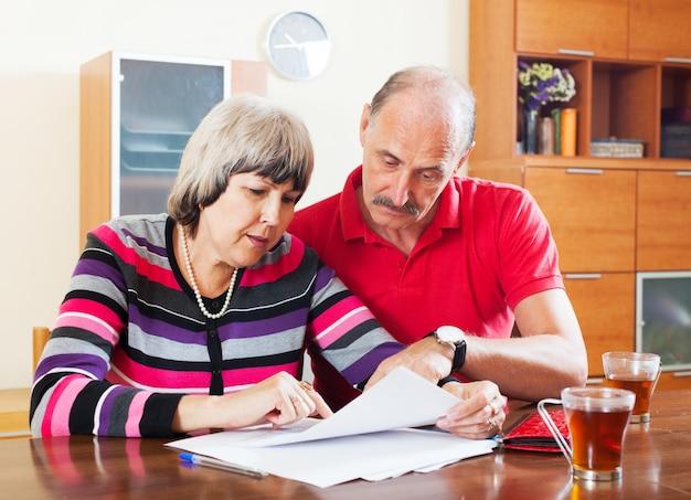 Couple mature, lecture de document financier