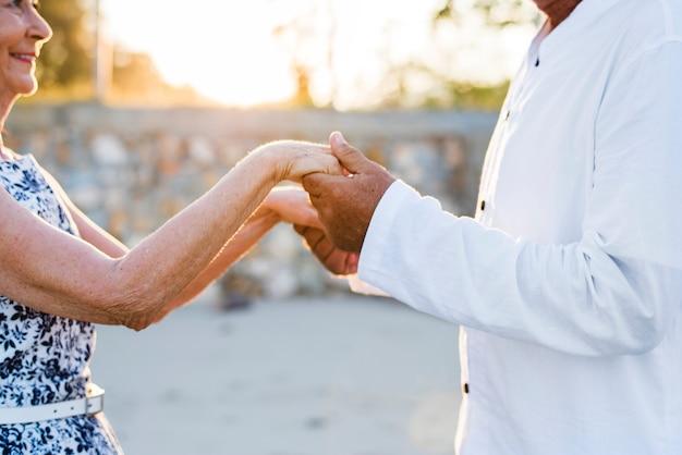 Couple mature tenant par la main au coucher du soleil