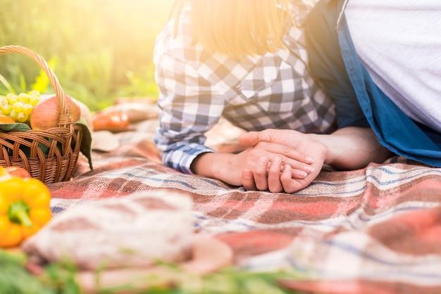 Couple méconnaissable allongé sur une couverture et main dans la main