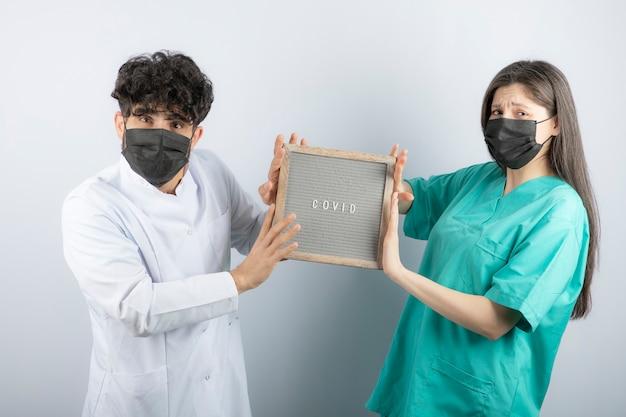 Couple de médecins en uniforme tenant un cadre et regardant la caméra.