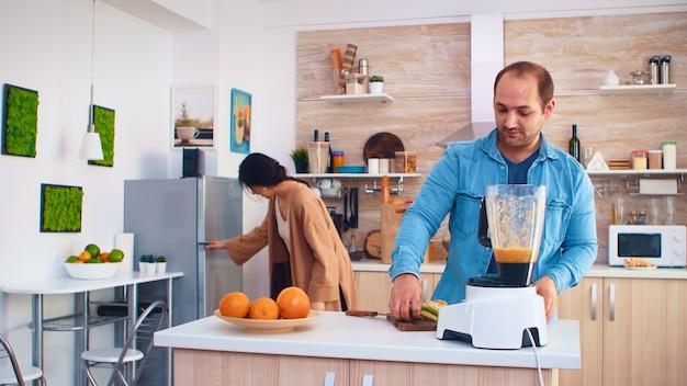 Couple mélangeant divers fruits pour un smoothie nutritif et sain dans la cuisine. joyeuse famille faisant ensemble du jus de fruits frais et nutritif bio sain pour le petit-déjeuner à partir de fruits frais tout en mourant