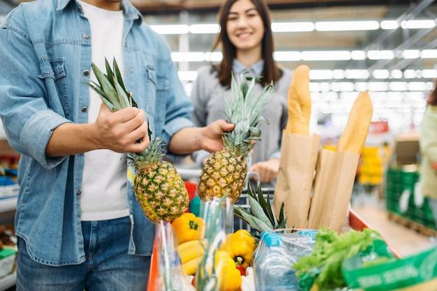 Couple met des ananas frais dans le panier avec des produits dans un supermarché, des achats en famille. client en magasin, acheteur sur le marché