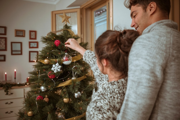 Couple, mettre, babioles, sur, arbre noël