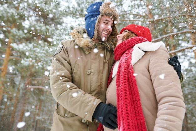 Couple mignon dans la forêt d'hiver