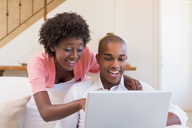 Couple mignon se détendre sur le canapé avec un ordinateur portable
