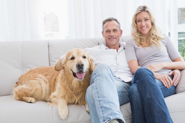 Couple mignon se détendre ensemble sur le canapé avec leur chien