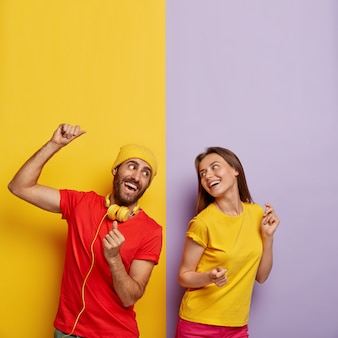 Couple millénaire positif posant contre le mur bicolore