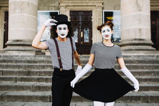 Couple mime, debout, devant, escalier, salutation