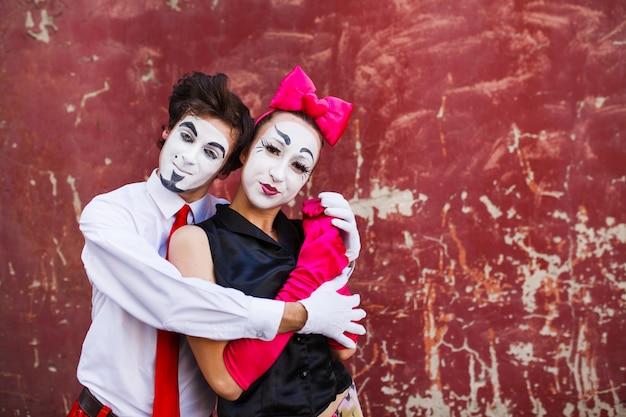 Couple mimes pose mignonne devant un mur rouge