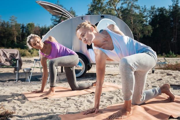 Couple mince. couple mince en bonne santé se sentant extrêmement soulagé et incroyable de faire du yoga dans la nature ensemble