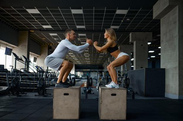 Couple mince faisant des exercices d'équilibre sur des cubes en salle de sport