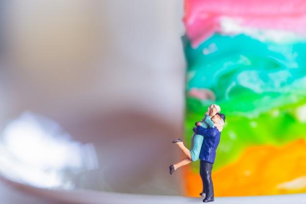 Couple miniature étreignant devant fond coloré.
