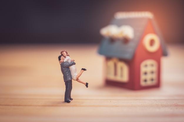 Couple miniature avec maison miniature sur bois