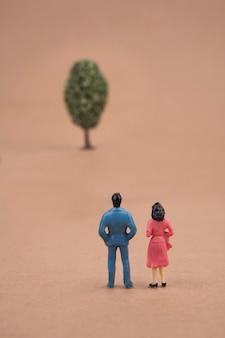 Couple miniature en regardant l'arbre sur brun