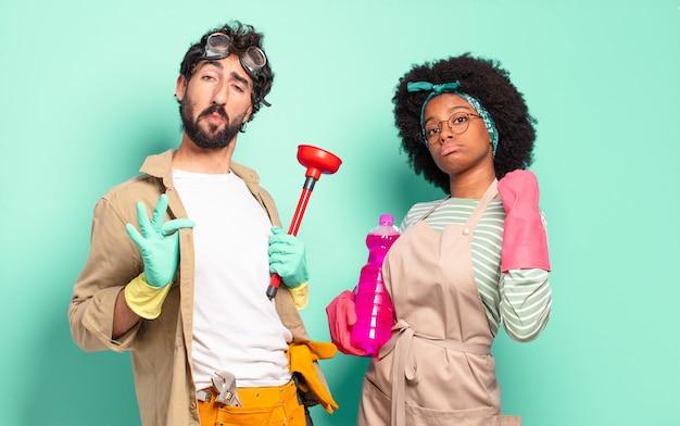 Un couple mixte à l'air arrogant, positif et fier des produits de nettoyage et des outils