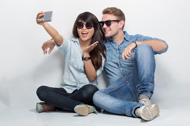 Couple mixte, séance terre, prendre, appareil-photo ensemble