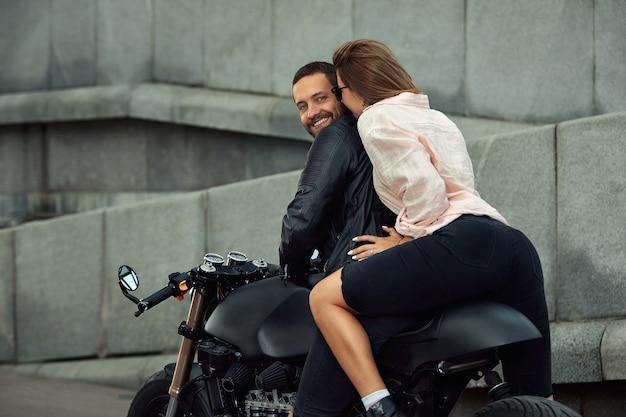 Couple de mode assis sur une moto, mur de pierre en arrière-plan. jeune homme et femme avec moto moderne.