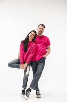 Couple à la mode branché isolé sur mur blanc