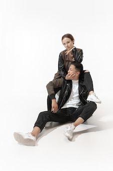Couple à la mode branché isolé sur mur de studio blanc