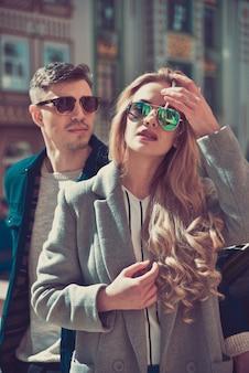 Couple à la mode dans des lunettes de soleil se tient à la rue près de la voiture