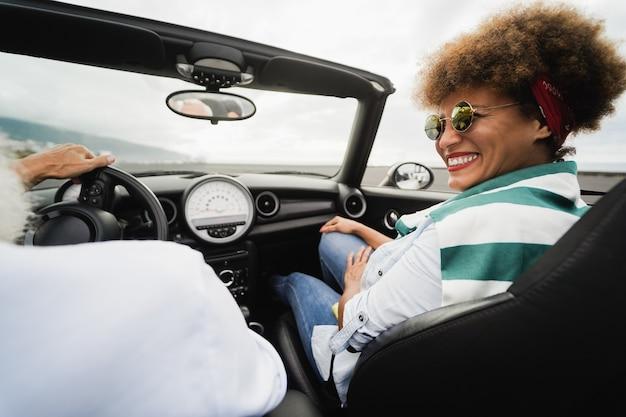 Couple à la mode senior à l'intérieur d'une voiture décapotable en vacances - focus sur le visage de la femme