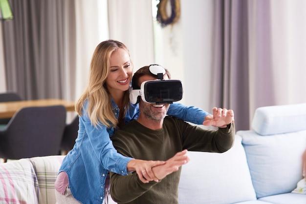 Couple moderne utilisant un simulateur de réalité virtuelle dans le salon