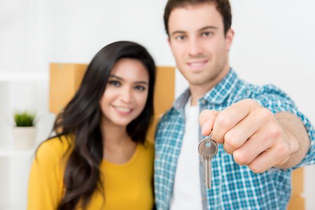 Couple montrant la clé après avoir déménagé dans une nouvelle maison