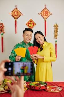 Couple montrant des enveloppes d'argent chanceux rouge et jaune