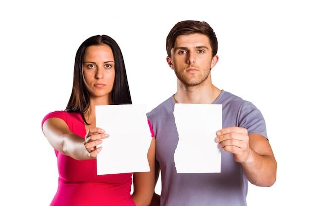 Couple montrant un morceau de papier cassé