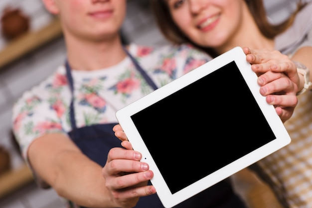 Couple montrant une tablette moderne ensemble